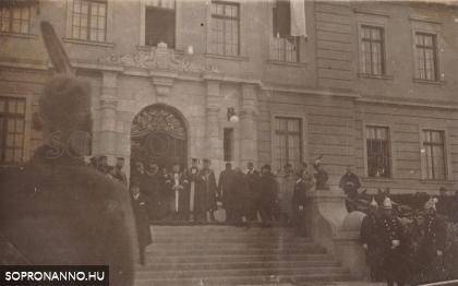 Elöljárók az épület bejárata előtt