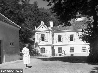 Janka néni az igazgatónő, háttérben az iskola épülete. Balra a gazdasági épület látható.